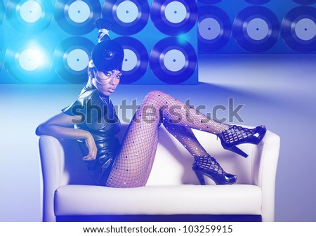 Attractive woman siting in white chair on vinyl records and neon light - stock photo