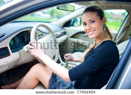 attractive woman sitting in driver seat in the car - stock photo