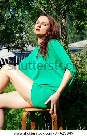 Attractive woman sitting in the garden and enjoying the sun - stock photo