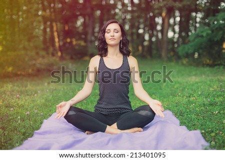 Attractive woman sitting meditating in the lotus position on a rug in a green field with trees with a relaxed serene expression and eyes closed - stock photo