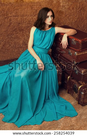 Attractive woman sitting next the pile of vintage suitcases. Travel concept - stock photo