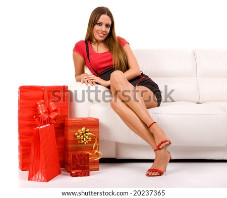 Attractive woman sitting on couch with present. - stock photo