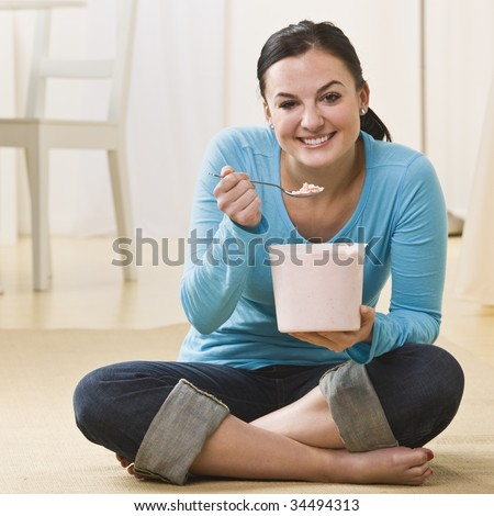 Attractive woman sitting on floor with crossed legs and eating ice cream. Square - stock photo