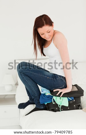 Attractive woman sitting on her suitcase in the bedroom - stock photo
