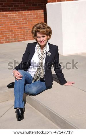 Attractive Woman Sitting on Steps Enjoying the Sun - stock photo