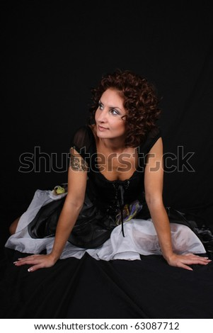 attractive woman sitting over black background