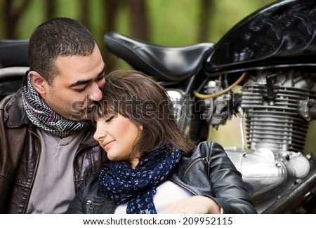 Attractive woman sleeping on shoulders of her husband, sitting near bike, relaxation after bikers tour in the forest, active and loving family concept - stock photo