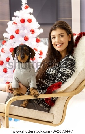 Attractive woman smiling happy holding dog on lap, sitting front of christmas tree. - stock photo