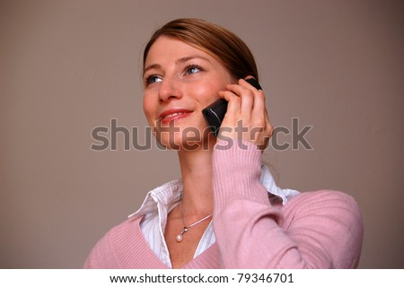 Attractive woman speaking on the phone and smiling, looking up - stock photo