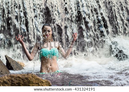 attractive woman splashes water on waterfall