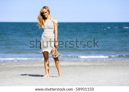 Attractive woman standing barefoot and holding shoes at beach, blue sky and ocean in background - stock photo