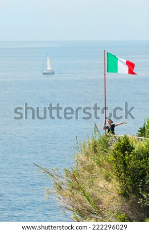 Attractive woman standing by the Italian flag, sea with yacht in the background - stock photo