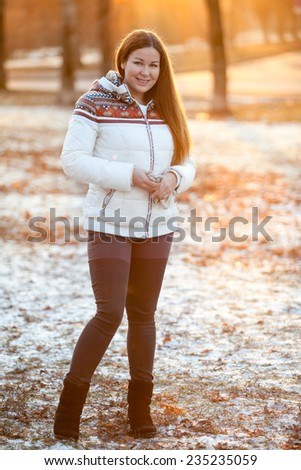 Attractive woman standing full-length in the park in sunlight of sunset sun - stock photo