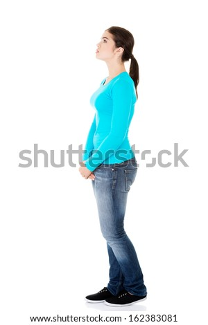 Attractive woman standing looking on copy space. Side view. Isolated on white.  - stock photo