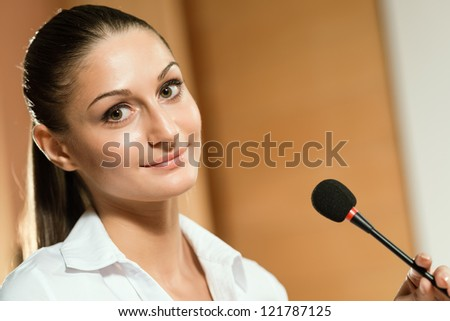 attractive woman standing near a microphone, preparing a speech, looking at the camera