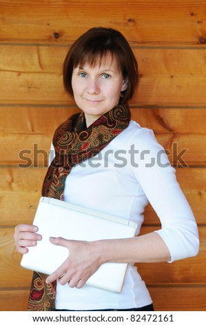 Attractive woman standing with laptop - stock photo