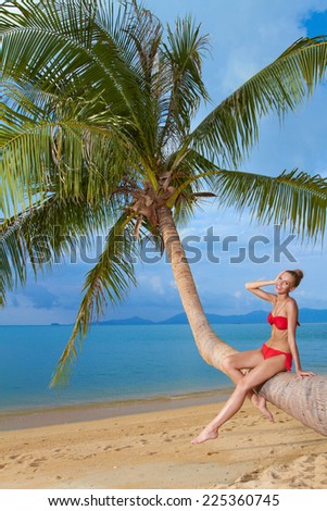 Attractive woman sunbathing on a palm tree sitting on the trunk in her red bikini overlooking a sandy tropical beach and calm blue ocean - stock photo