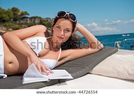Attractive woman sunbathing on luxury boat reading book in bikini - stock photo
