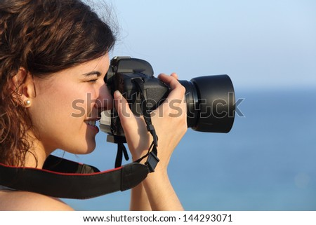 Attractive woman taking a photograph with her camera with the sea in the background - stock photo