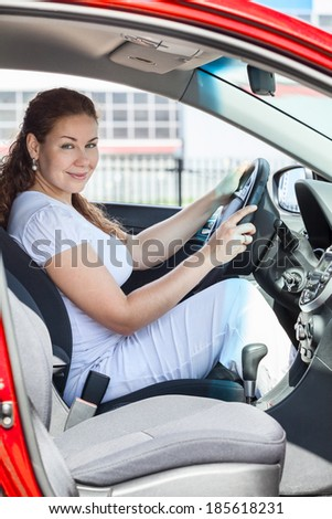 Attractive woman through the opened door sitting in red car - stock photo