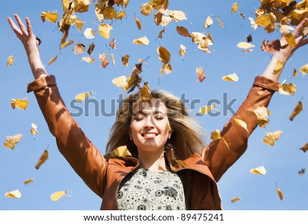 Attractive woman throw up autumnal leaves - stock photo