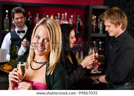 Attractive woman toast champagne with friends at cocktail bar - stock photo