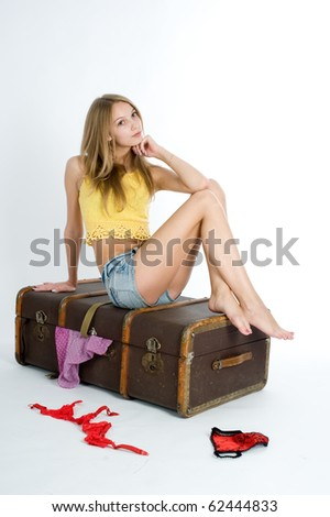 Attractive woman trying to close her suitcase - stock photo