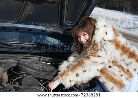 Attractive woman trying to fix the car - stock photo