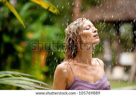Attractive woman under tropical rain in an exotic garden. - stock photo