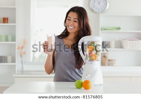 Attractive woman using a blender while holding a drink in the kitchen - stock photo