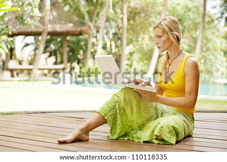 Attractive woman using a laptop computer in a hotel tropical garden near a swimming pool. - stock photo