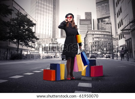 Attractive woman using a mobile phone and carrying some shopping bags on a city street - stock photo