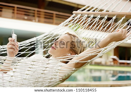 Attractive woman using an mp4 player to listen to music with headphones while laying in a hammock near a swimming pool. - stock photo