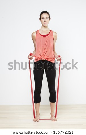 Attractive woman using sports elastic bands in the gym