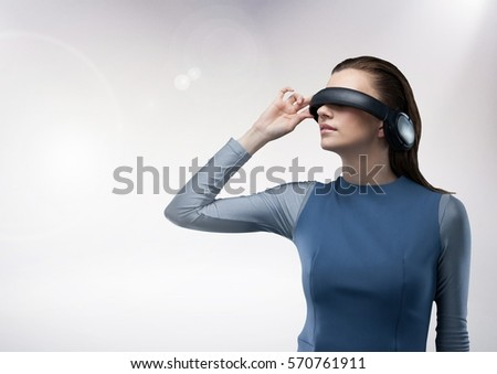 Attractive woman using virtual reality headset against white background
