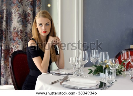 attractive woman waiting for someone at the restaurant table - stock photo