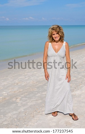 Attractive Woman Walking on the Beach in a Sundress - stock photo