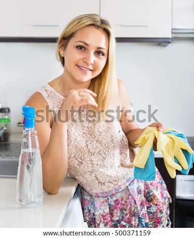 Attractive woman washing a kitchen top with the detergent