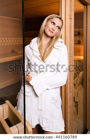 Attractive woman wearing a short white bathrobe is posing while leaving the sauna through a partly opened glass door - stock photo