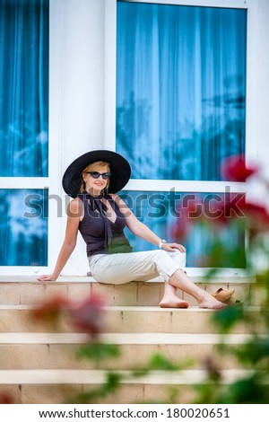 Attractive woman wearing big black hat  - stock photo