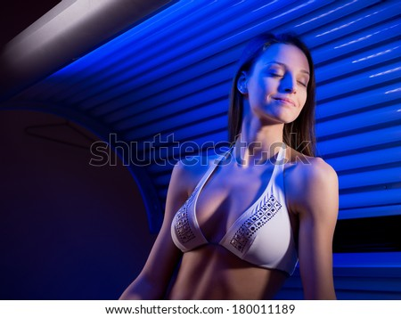 Attractive woman wearing bikini and sitting on tanning bed. - stock photo