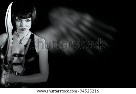 attractive woman wearing black with sword and angel wings - stock photo