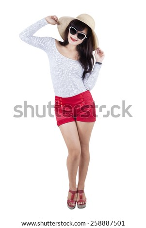 Attractive woman wearing modern style clothes, standing in the studio isolated over white - stock photo