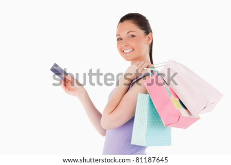 Attractive woman with a credit card holding shopping bags while standing against a white background
