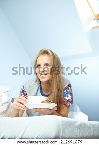 Attractive woman with a cup of coffee on the bed  - stock photo