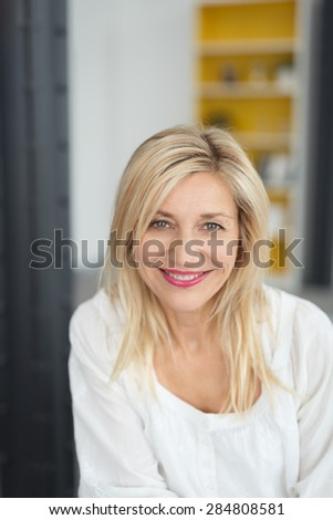 Attractive woman with a lovely warm friendly smile looking directly at the camera with a happy expression, indoors at home - stock photo