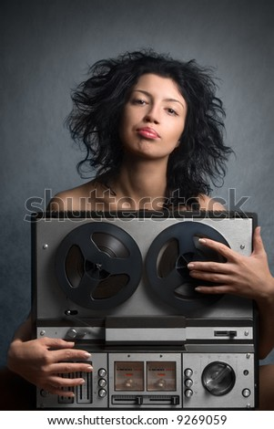 Attractive woman with a retro audio tape recorder - stock photo