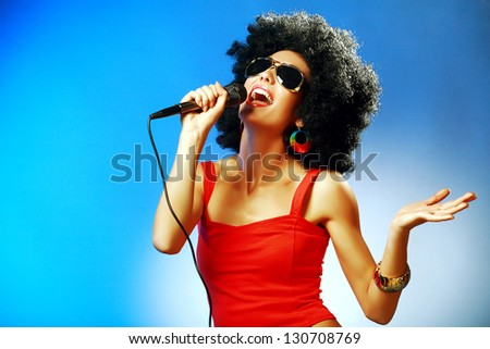 Attractive woman with afro hairstyle is singing expressively into the the microphone against blue background - stock photo