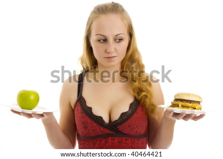 Attractive woman with an apple and burger on the plates in her hand. Isolated.