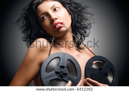 Attractive woman with an audio retro bobbins on a brest - stock photo
